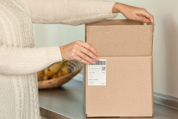 Young woman unpacking parcel indoors