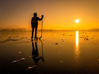 Ice hockey player on a frozen lake at sunset