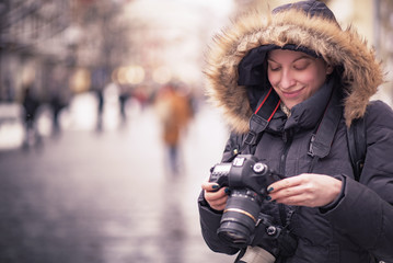 Young female tourist photographing street of a foreign city, Belgrade - capital of Serbia, during winter time, christmas and new year's holiday