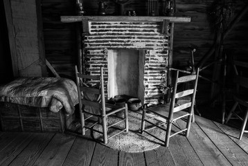 wooden chairs at the fireplace of an old log cabin