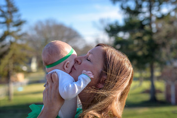 woman kissing baby on St. Patrick's Day