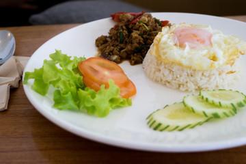 Fried basil leave with pork, squid, shrim, chicken, meat, crisp pork, chicken innards, combination on rice.