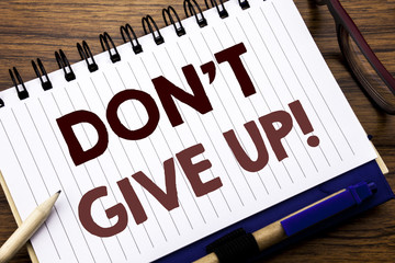 Hand writing text caption inspiration showing Don t Give Up. Business concept for Motivation Determination, Written on notebook note paper, wooden background with glasses pen and marker.