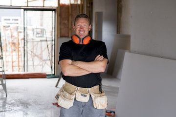 attractive and confident constructor carpenter or builder man with ear protection gear working happy at industrial construction site