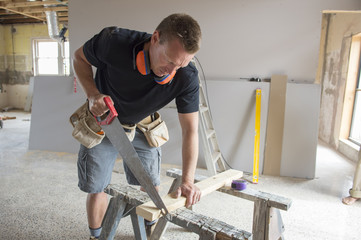 attractive and confident constructor carpenter or builder man working cutting wood with manual saw in industrial construction job concept