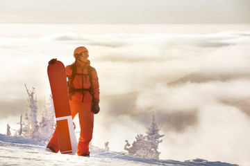 Snowboarding concept with man and snowboard against mountain top