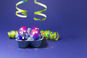 Group of colorful painted Easter eggs with funny cartoon style faces in a light blue egg box, colorful confetti and paper streamers on purple background