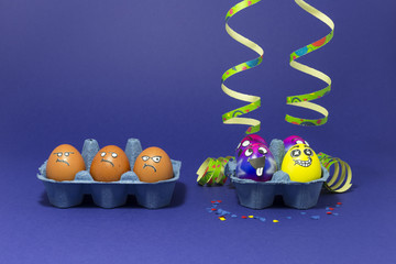 Group of colorful painted Easter eggs with funny cartoon style faces, confetti and paper streamers and group of grumpy looking brown eggs in light blue egg boxes on purple background