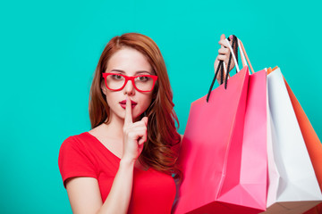 Young beautfiul redhead girl in eyeglasses with shopping bags
