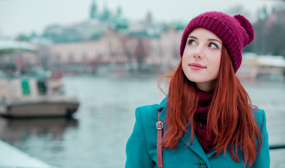 Portriat of young redhead girl in hat and coat in Prague