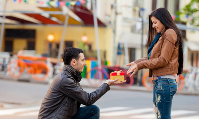 Young man giving a gift as to a young girl