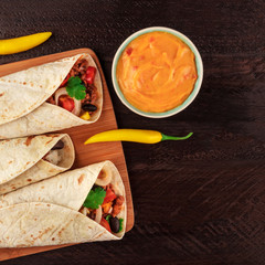 Mexican burritos with cheese salsa, chili peppers, and copyspace, square photo