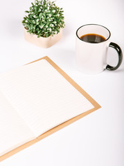Blank notebook with cup of coffee and flowers