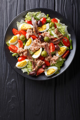 Delicious gourmet nicoise salad with vegetables, eggs, tuna and anchovies close up on a plate. Vertical top view