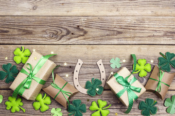 Background with  horseshoe, clover leaves and gift boxes on the old wooden boards. Space for text.