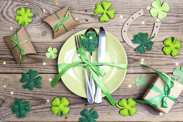 Festive table setting for St.Patrick's day with cutlery and lucky symbols on wooden table.