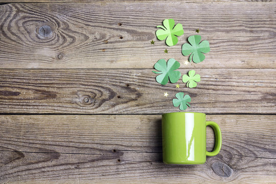 Green mug with four-leaf clover on wooden background. Copy space, top view.