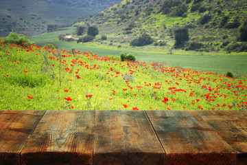wooden rustic table in front of field red poppies. product display and picnic concept.