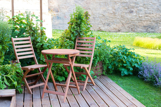 empty wood table and chairs on the terrace at summer day