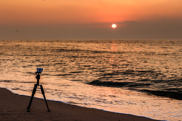Action Camera on a sandy beach shooting a video of sunset over the sea.