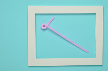 Pink cocktail tube in a white frame on a blue pastel background. Copy space. Minimalist trend..