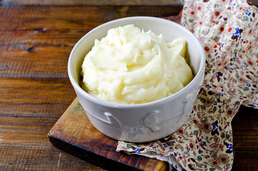 Mashed potatoes in a bowl on a wooden table