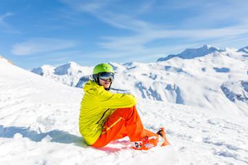 Photo of sportive man wearing helmet wearing yellow jacket sitting on snowy slope
