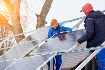Smiling technicians mounting blue solar modules on roof of modern house as a sustainable source of alternative energy. Renewable electricity photovoltaic panel sun power plant ecological