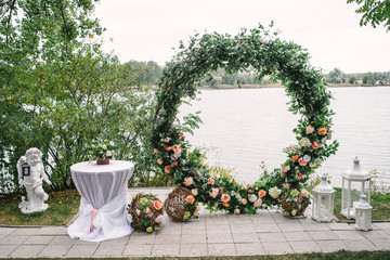 Beautiful round wedding arch decorated with flowers and greenery near lake or river outdoors, copy space. Decorations for wedding ceremony in open air