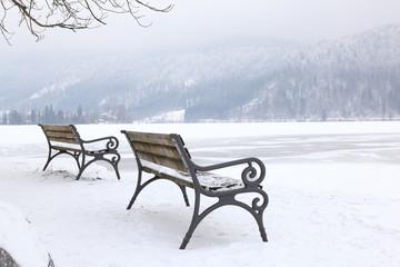 Bänke am gefrorenen Seeufer in den Bergen im Winter