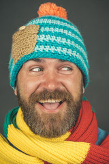 Smiling handsome bearded man, sexy guy in knitted hat and scarf. Winter fashion. Brutal caucasian hipster, bearded man with long beard, with beard and moustache wearing hat and scarf.