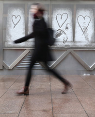 A woman walks past hearts that have been drawn in the snow, in Canary Wharf financial district, London