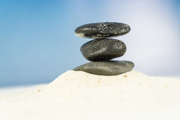 Three black stones in the sand, blue sky background