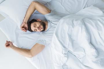 top view of handsome man sleeping on bed in bedroom