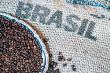 coffee beans on jute sack and printed Brasil on background