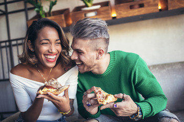 Mixed race couple eating pizza in modern cafe. They are laughing and eating pizza and having a great time.
