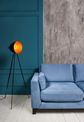 Vintage lamp and blue sofa in minimalistic interior