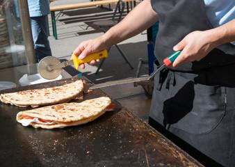 Preparazione piadina con prosciutto crudo, prodotto tipico italiano, fuoco selettivo