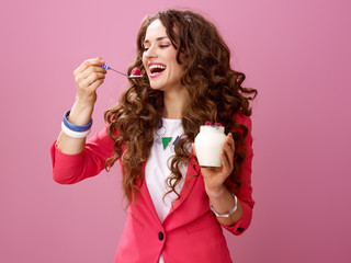 smiling woman isolated on pink eating farm organic yogurt
