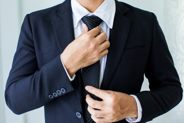People, business,fashion and clothing concept - close up of man in shirt dressing up and adjusting tie on neck at home. Fotobehang