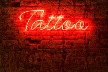 Glowing red neon signboard word tattoo on a brick dark background.