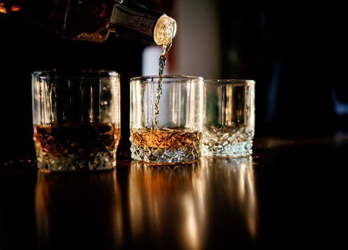 Man pours whisky in the glasses standing before a wooden table
