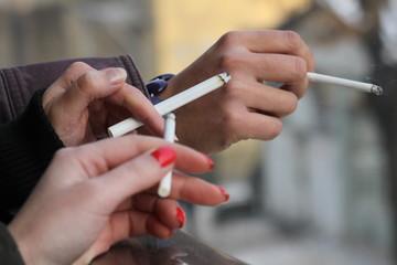 Cigarettes. Young women smoke cigarettes. Smoking cigarette . Young people smoke cigarettes