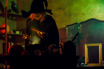 Image of witch in black hat reading spell over pot of green steam