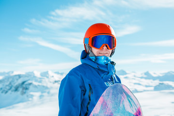 Picture of sports man in helmet with snowboard on background of snowy hill