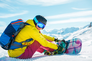 Image of woman in helmet with backpack sitting in snow with snowboard