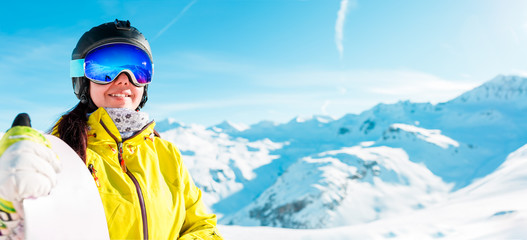 Panoramic image of woman in helmet and with snowboard against background of snowy landscape