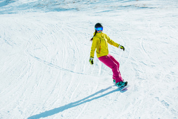 Picture of young woman in helmet riding snowboard on snowy mountain