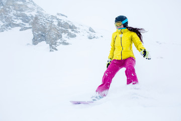 Photo of athlete girl in helmet with developing hair, snowboarding from mountain slope