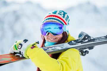Portrait of woman in mask with skis on her shoulder standing sideways